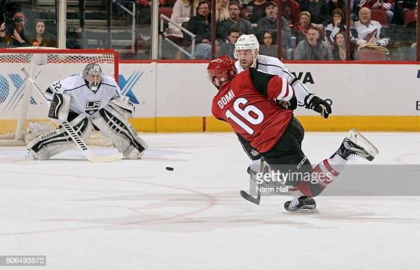 Max Domi of the Arizona Coyotes shoots the puck toward goalie Jonathan Quick of the Los Angeles Kings as Alec Martinez of the Kings defends during...