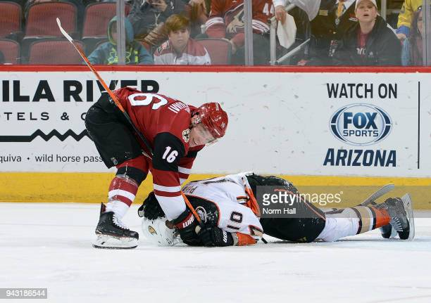 Max Domi of the Arizona Coyotes tries to get his stick from under Corey Perry of the Anaheim Ducks during the second period at Gila River Arena on...