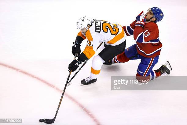 Max Domi of the Montreal Canadiens is hurt as he is called for holding on Scott Laughton of the Philadelphia Flyers during the second period in Game...