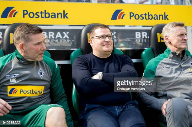 Max Eberl sits next to Uwe Kamps and Doctor Stefan Hertl on the bench during the Bundesliga match between Borussia Moenchengladbach and Hertha BSC at...