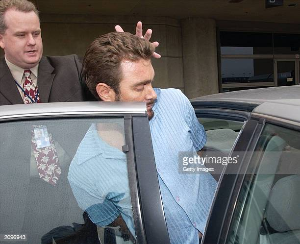 Max Factor cosmetics heir Andrew Luster is guided into a car by a law enforcement officer June 19 2003 after arriving at the Los Angeles...