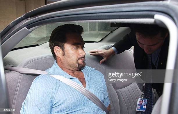 Max Factor cosmetics heir Andrew Luster is held in a car by law enforcement officers June 19 2003 after arriving at the Los Angeles International...