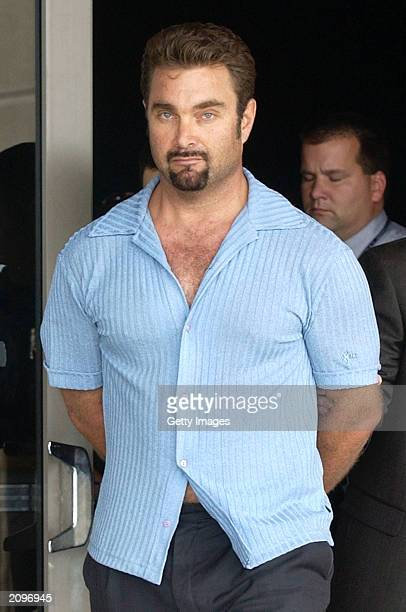 Max Factor cosmetics heir Andrew Luster is led to a car by a law enforcement officer June 19 2003 after arriving at the Los Angeles International...