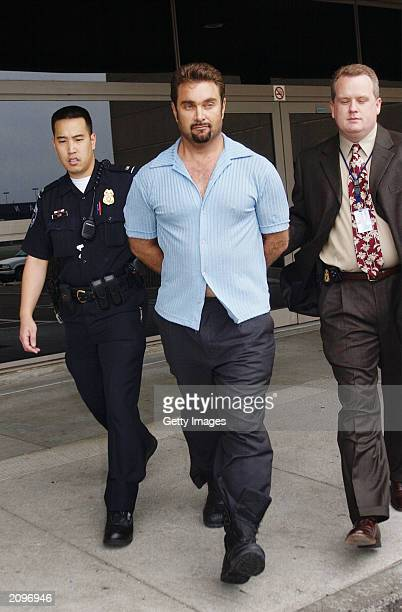 Max Factor cosmetics heir Andrew Luster is led to a car by law enforcement officers June 19 2003 after arriving at the Los Angeles International...