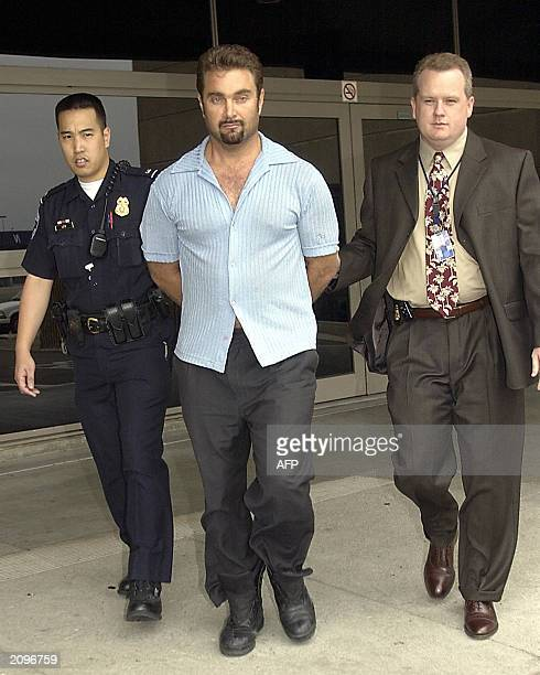 Max Factor fortune heir Andrew Luster is brought out of the Los Angeles International Airport under the custody of airport police and FBI agents...