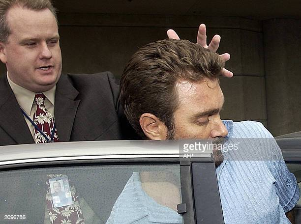 Max Factor fortune heir Andrew Luster is helped into a car by an unidentified FBI agent 19 June after arriving at Los Angeles International Airport...