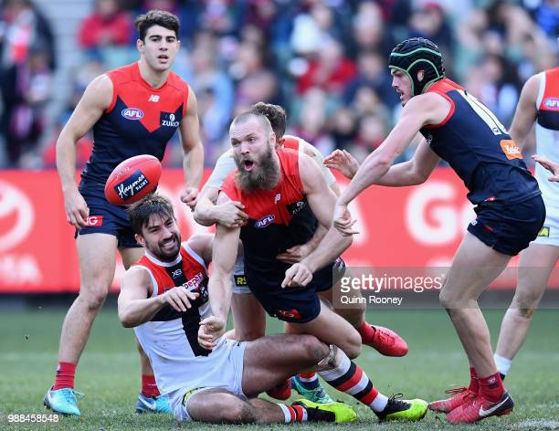 Max Gawn of the Demons handballs whilst being tackled by Billy Longer of the Saints during the round 15 AFL match between the Melbourne Demons and...