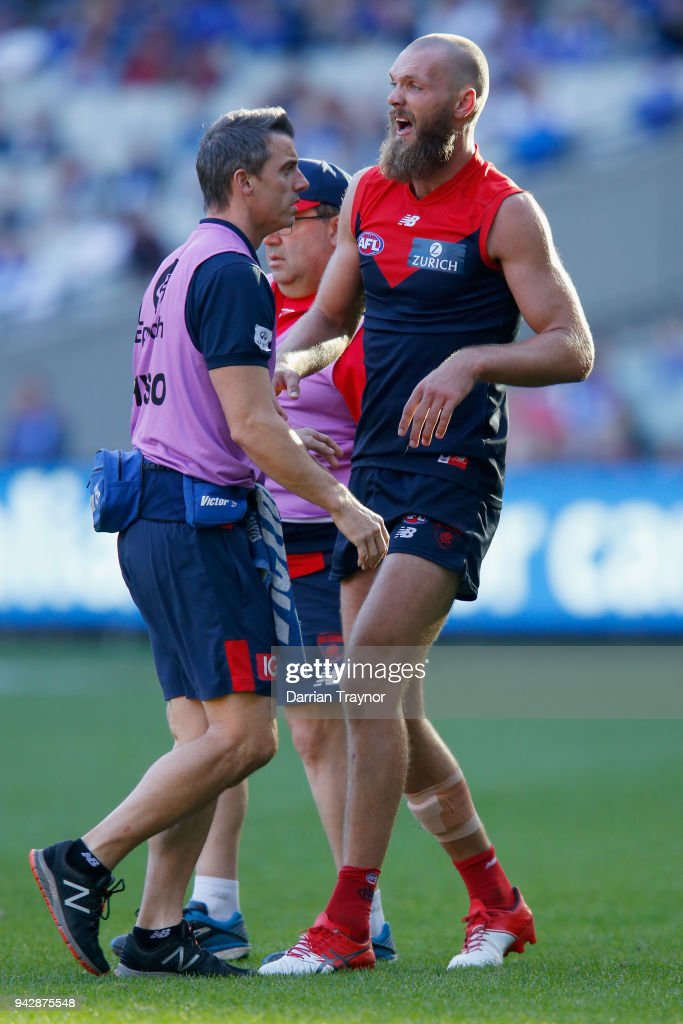 Max Gawn of the Demons is helped by trainers during the round three AFL match between the Melbourne Demons and the North Melbourne Kangaroos at Melbourne Cricket Ground on April 7, 2018 in Melbourne, Australia.