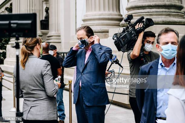 Max Hollein, director of the Metropolitan Museum of Art, center, adjusts his mask while speaking to members of the media during the public reopening...