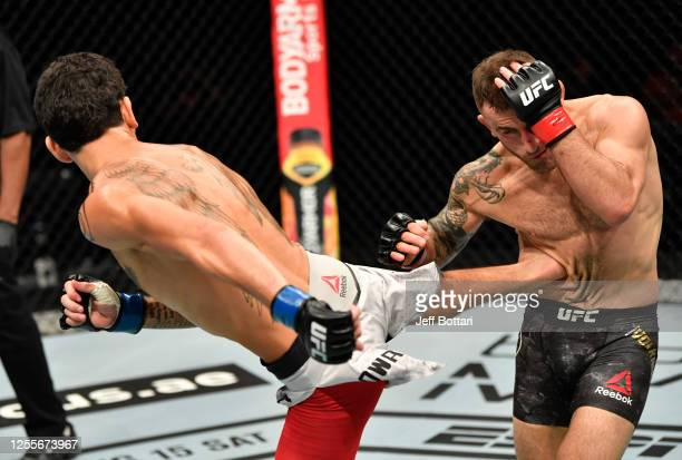 Max Holloway kicks Alexander Volkanovski of Australia in their UFC featherweight championship fight during the UFC 251 event at Flash Forum on UFC...