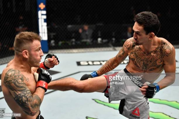 Max Holloway kicks Alexander Volkanovski of Australia in their UFC featherweight championship fight during the UFC 251 event at Flash Forum on UFC...