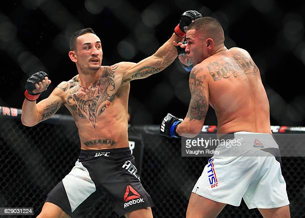 Max Holloway of the United States fights Anthony Pettis of the United States for the Interim Featherweight Title during the UFC 206 event at Air...