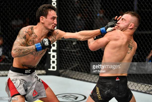 Max Holloway punches Alexander Volkanovski of Australia in their UFC featherweight championship fight during the UFC 251 event at Flash Forum on UFC...