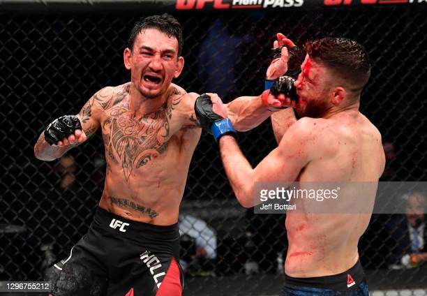 Max Holloway punches Calvin Kattar in a featherweight bout during the UFC Fight Night event at Etihad Arena on UFC Fight Island on January 17, 2021...