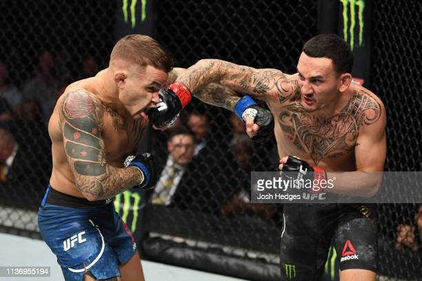Max Holloway punches Dustin Poirier in their interim lightweight championship bout during the UFC 236 event at State Farm Arena on April 13, 2019 in...