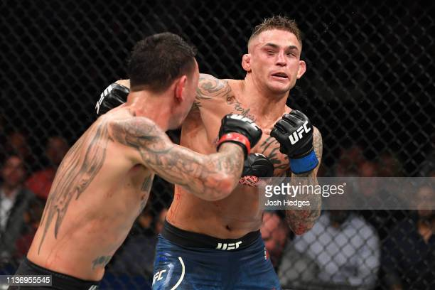 Max Holloway punches Dustin Poirier in their interim lightweight championship bout during the UFC 236 event at State Farm Arena on April 13 2019 in...