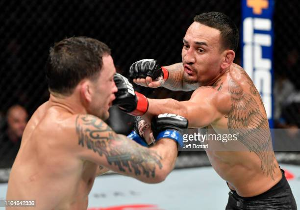 Max Holloway punches Frankie Edgar in their UFC featherweight championship bout during the UFC 240 event at Rogers Place on July 27, 2019 in...