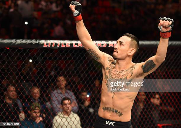Max Holloway signals to the crowd as he enters the Octagon prior to facing Jose Aldo of Brazil in their UFC featherweight championship bout during...