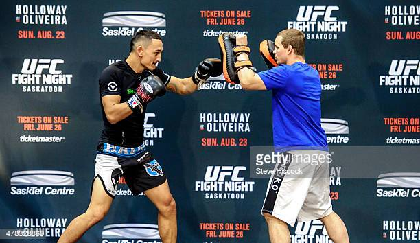 Max Holloway works out with a trainer at a press conference at the SaskTel Centre June 24 2015 in Saskatoon Saskatchewan Canada