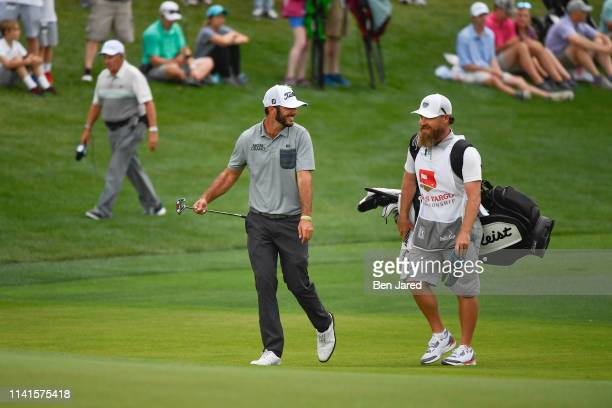 Max Homa laughs with his caddie Joe Greiner while walking on the eighteenth fairway during the final round of the Wells Fargo Championship at Quail...