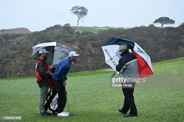 Max Homa speaks with a rules official as a hailstorm hits the course during round two of the Farmers Insurance Open at Torrey Pines on January 29,...