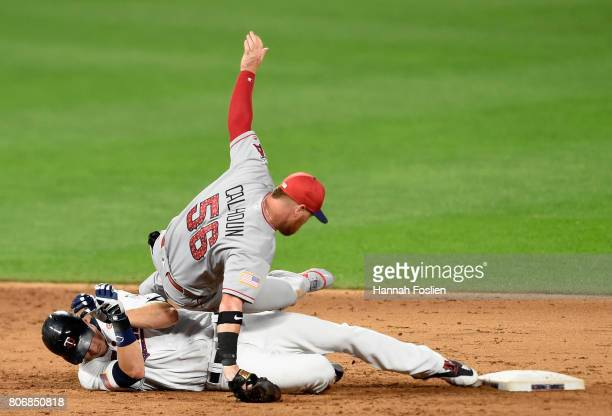 Max Kepler of the Minnesota Twins is safe at second base as Kole Calhoun of the Los Angeles Angels of Anaheim trips over him during the sixth inning...