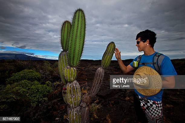 Max Kohrman tourist touching a cactus on the lava bed Isabella Island Punta Moreno Galapagos