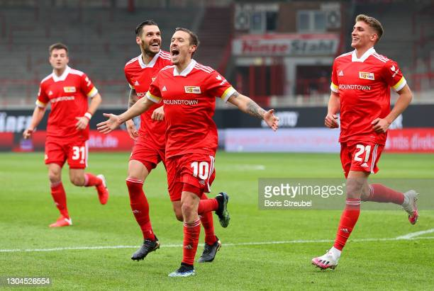 Max Kruse of 1.FC Union Berlin celebrates with teammates Christopher Trimmel and Grischa Proemel after scoring their team's first goal during the...