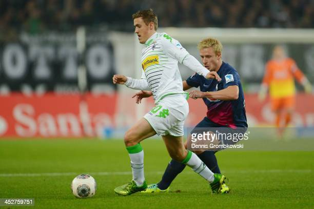 Max Kruse of Borussia Moenchengladbach is challenged by Mike Hanke of SC Freiburg during the Bundesliga match between Borussia Moenchengladbach and...