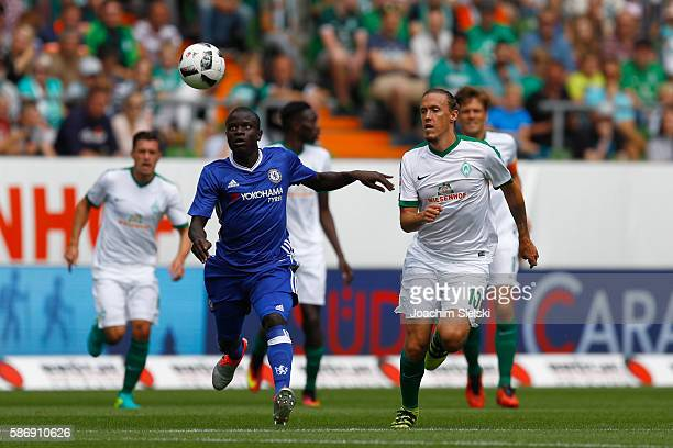 Max Kruse of Bremen challenges N Golo Kante of Chelsea during the preseason friendly match between Werder Bremen and FC Chelsea at Weserstadion on...