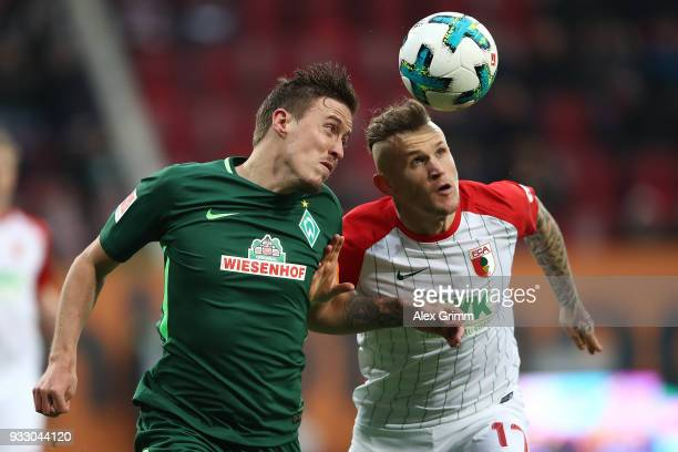 Max Kruse of Bremen l fights for the ball with Jonathan Schmid of Augsburg during the Bundesliga match between FC Augsburg and SV Werder Bremen at...