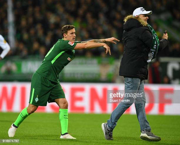 Max Kruse of Bremen pushes away a pitch invaider during the Bundesliga match between SV Werder Bremen and VfL Wolfsburg at Weserstadion on February...