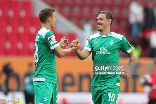 Max Kruse of Bremen shakes hands with Niklas Moisander of Bremen during the Bundesliga match between FC Augsburg and SV Werder Bremen at WWKArena on...