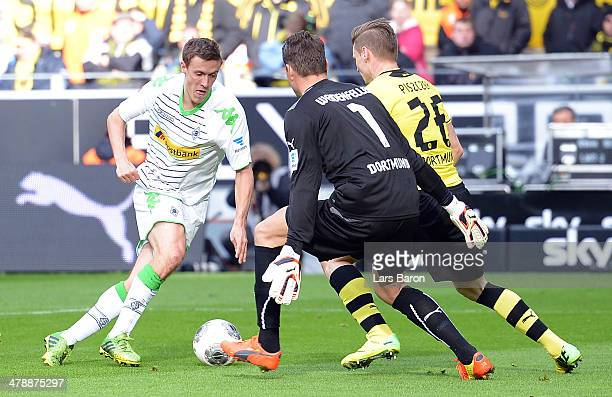 Max Kruse of Moenchengladbach is on his way against goalkeeper Roman Weidenfeller and Lukasz Piszczek of Dortmund to score his teams second goal...