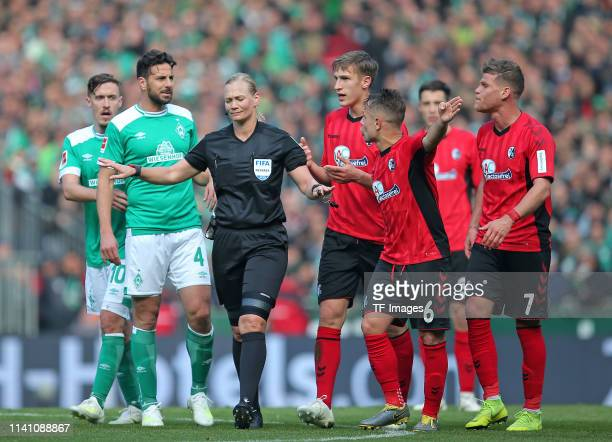 Max Kruse of SV Werder Bremen and Claudio Pizarro of SV Werder Bremen speak with referee Bibiana Steinhaus during the Bundesliga match between SV...