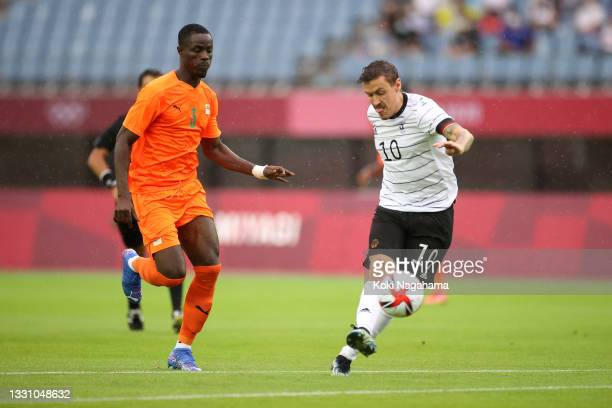 Max Kruse of Team Germany shoots whilst under pressure from Eric Bailly of Team Ivory Coast during the Men's Group D match between Germany and Cote...