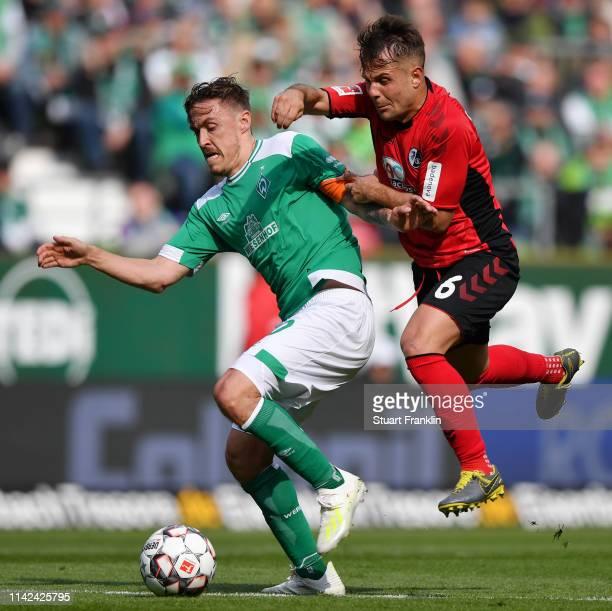 Max Kruse of Werder Bremen is challenged by Amir Abrashi of Freiburg during the Bundesliga match between SV Werder Bremen and SportClub Freiburg at...