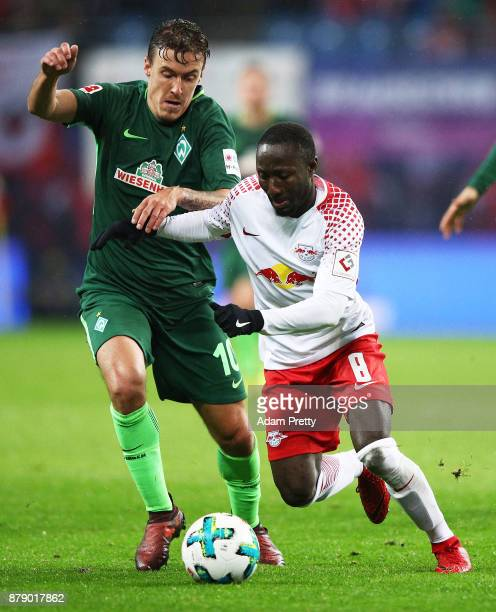 Max Kruse of Werder Bremen tackles Naby Keita of RB Leipzig during the Bundesliga match between RB Leipzig and SV Werder Bremen at Red Bull Arena on...