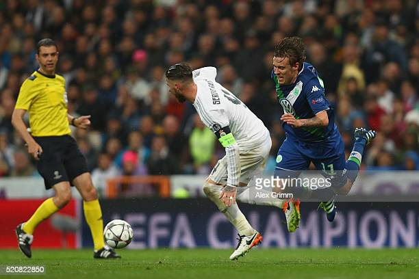 Max Kruse of Wolfsburg is challenged by Sergio Ramos of Real Madrid during the UEFA Champions league Quarter Final Second Leg match between Real...