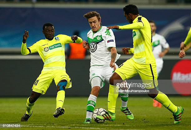 Max Kruse of Wolfsburg is tackled by Nana Asare and Renato Neto of KAA Gent during the UEFA Champions League round of 16 first leg match between KAA...