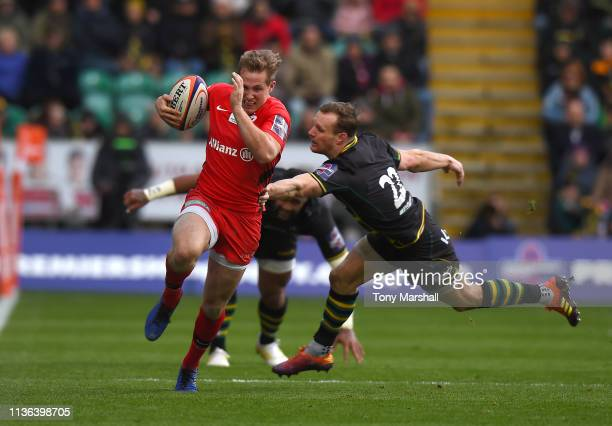 Max Malins of Saracens escapes a tackle by Rory Hutchinson of Northampton Saints during the Premiership Rugby Cup Final match between Northampton...