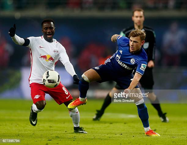 Max Meyer of FC Schalke 04 is challenged by Naby Keita of RB Leipzig during the Bundesliga match between RB Leipzig and FC Schalke 04 at Red Bull...