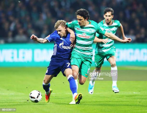 Max Meyer of Schalke 04 is tackled by Thomas Delaney of Werder Bremen during the Bundesliga match between Werder Bremen and FC Schalke 04 at...