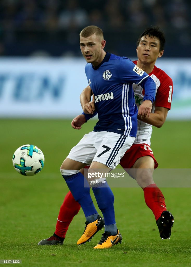Max Meyer (L) of Schalke and Koo Ja Cheol of Augsburg battle for the ball during the Bundesliga match between FC Schalke 04 and FC Augsburg at Veltins-Arena on December 13, 2017 in Gelsenkirchen, Germany.
