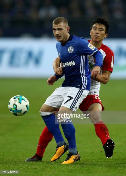 Max Meyer of Schalke and Koo Ja Cheol of Augsburg battle for the ball during the Bundesliga match between FC Schalke 04 and FC Augsburg at...