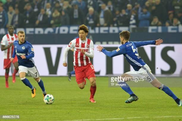 Max Meyer of Schalke and Yuya Osako of Koeln and Matija Nastasic of Schalke battle for the ball during the Bundesliga match between FC Schalke 04 and...