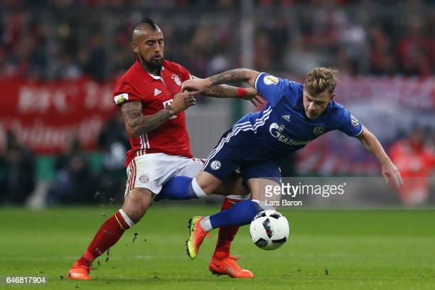 Max Meyer of Schalke is challenged by Arturo Vidal of Muenchen during the DFB Cup quarter final between Bayern Muenchen and FC Schalke 04 at Allianz...