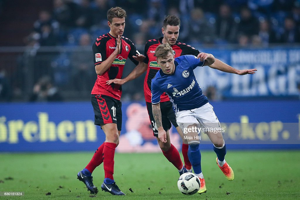 Max Meyer (R) of Schalke is challenged by Janik Haberer (L) and Christian Guenter of Freiburg during the Bundesliga match between FC Schalke 04 and SC Freiburg at Veltins-Arena on December 17, 2016 in Gelsenkirchen, Germany.