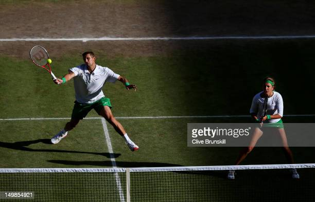 Max Mirnyi of Belarus plays a forehand next to his partner Victoria Azarenka of Belarus during their Mixed Doubles Tennis gold medal match against...