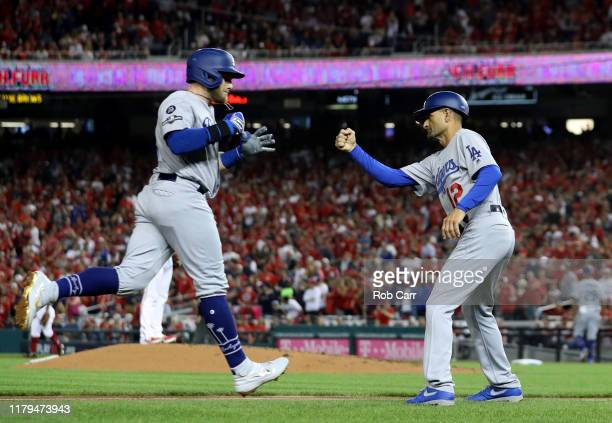 Max Muncy of the Los Angeles Dodgers celebrates his solo home run with third base coach Dino Ebel in the fifth inning of Game 3 of the NLDS against...
